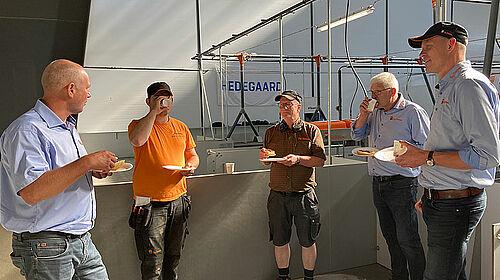 Fem herrer spiser og drikker kaffe i stalden og snakker